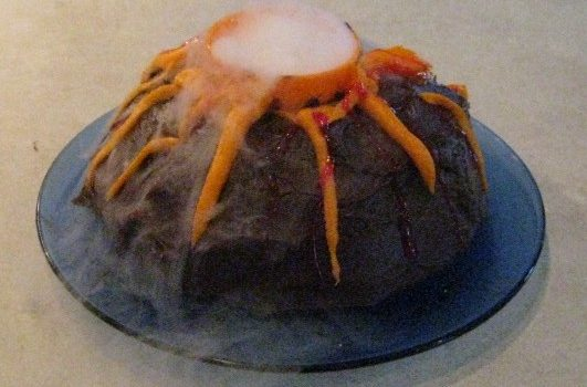 Add a little water to dry ice to make a smoking volcano effect on a cake. You can use red jello or tinted icing if you want 'lava' to flow down the sides of the cake.