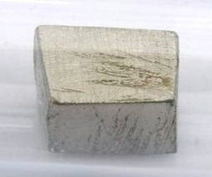 This is a chunk of pure praseodymium metal under a protective argon atmosphere. Praseodymium is a soft silvery metal that develops a green oxide coating that spalls off when exposed to air. Tomihahndorf