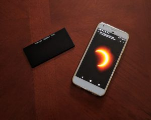 Place eclipse glasses or welder's glass over a cell phone to photograph a solar eclipse.