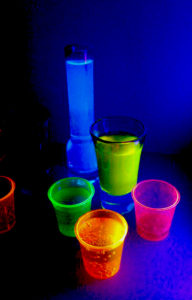 You can enhance the glow of highlighter ink by putting it in fluorescent plastic containers.