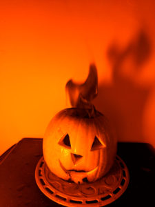 Shine a low pressure sodium lamp on a flame colored with table salt for a black flame pumpkin.