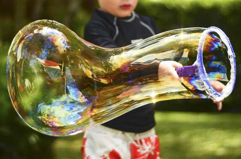 Twist together pipe cleaners to make a giant bubble wand similar to this store-bought plastic version.
