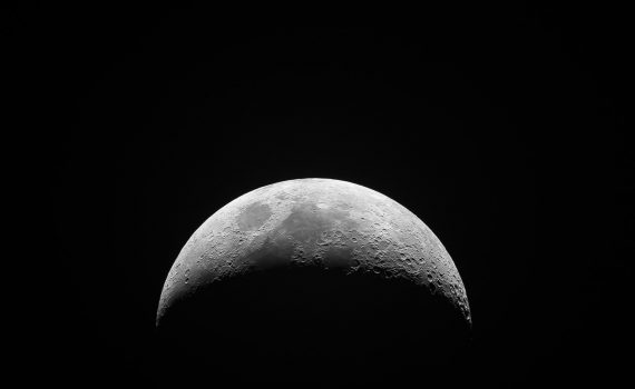 The moon rotates, completing one rotation each month so we only see one side.